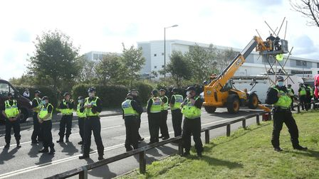 Police maintain a loose cordon as emergency services use a cherry picker to attempt to remove protes
