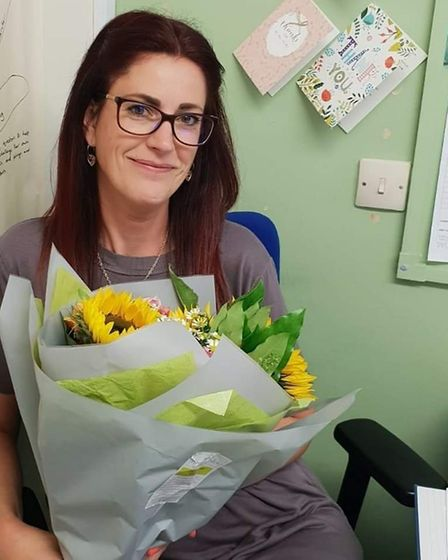 Pippa holding flowers and chocolate given to her by one of the children she provides therapy session