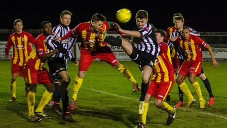 Sam Borrer challenges for a high ball in the black and white colours of Dereham Town. Picture: NEIL