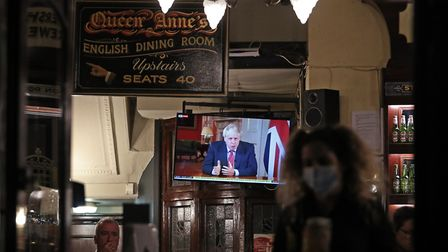 Customers at the Westminster Arms pub in London watch prime minister Boris Johnson address the natio
