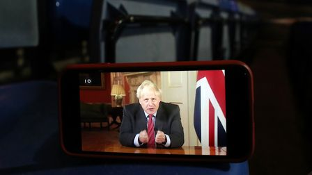 A video of prime minister Boris Johnson addressing the nation about coronavirus on the screen of a m