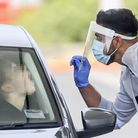 A member of staff testing a member of the public for coronavirus. Picture: PA