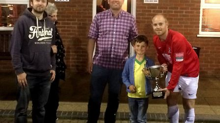 Luke Tuttle, right, shows off Dereham Town's Colin Wright Memorial Cup prize. Picture: SUBMITTED