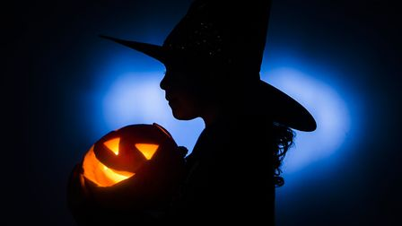 A young girl in a Halloween costume holds a pumpkin, ahead of Halloween Photo: Danny Lawson/PA Wire