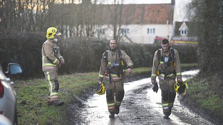 Fire fighters walking down the road close to the fire at Scarning on Monday afternoon. Picture: Ian