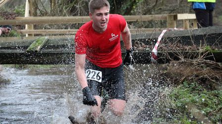 Dereham Road Runner Ash Gilbert wades in at the Reepham Cross Country Charity 10k. Picture: Andy Haw