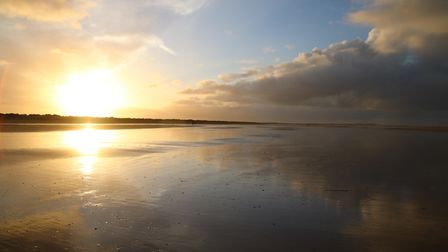 The clouds are reflected in the wet sand at Brancaster Beach Photo: Martin Sizeland