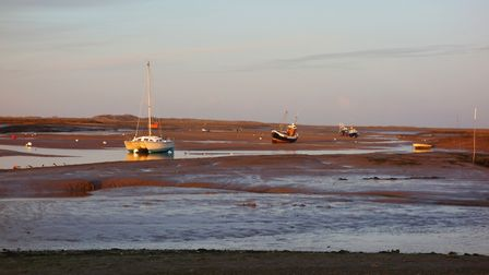 The late afternoon sun casts a warm light over Brancaster Harbour at rest Photo: John Daynes