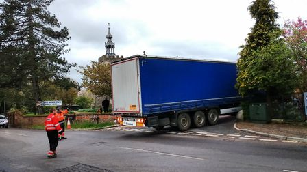 A lorry reverses out of Church Lane having been pulled out of a field, where it toppled over