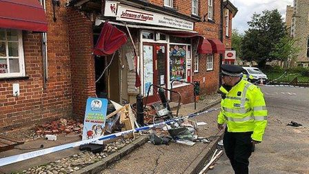 Police on the scene of a ram raid at a Post Office in Reepham, working to remove a JCB that was used