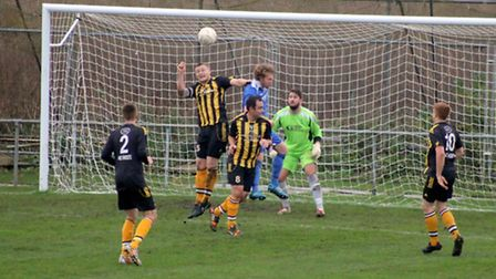 Matt Gilchrist heads the ball away during Fakenham Town's FA Vase defeat at Yaxley. Picture: TONY MI