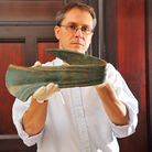 Dr Tim Pestell with the Bronze Age dirk (large dagger) which was ceremonially bent when it was made.