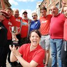 Team Captain for Norwich Street Rebecca Codman lifts the trophy surrounded by some of her winning te