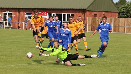 Fakenham Town's Sam Garner tries to nick the ball from the Yaxley keeper. Picture: TONY MILES
