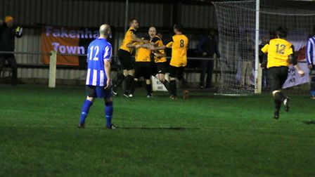 Fakenham Town's players mob Robbie Harris after his late, late equaliser. Picture: TONY MILES