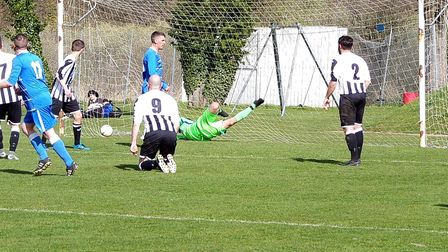 The Acle United Reserves keeper is unable to stop Wells Town's second goal going in. Picture: RICHA
