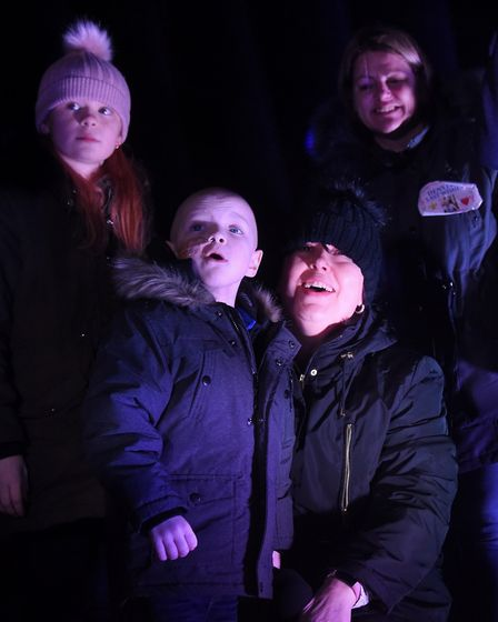 Denver Clinton wowed by the Dereham Christmas lights after he pulled the switch. With him are his fa