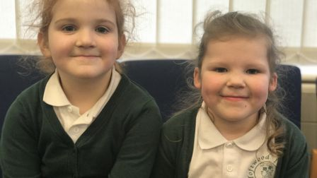 Year 1 pupils Ruby, who wears hearing aids, left, and Isobel, who has a cochlear implant, right, too