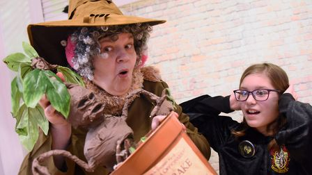 Professor Sprout (Marion Broughton) with a mandrake plant and Taliyah Moutinho, 11, as Neatherd High
