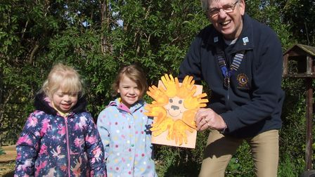 Marham Village Pre-school members Izzy and Madison presenting Swaffham and District Lions Club presi