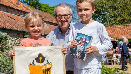 Paddy Clabburn (Right) & India Clabburn (Left) buy the 50,000 Charity Book from Rob Metcalfe (Centr