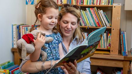 Kate Bunkall chooses a book for daughter Florence at the Morston Charity Book Sale. Photo: Lee Blanc
