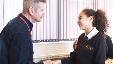 Author Terry Sewell handing out a prize to Year Eight student Alice Hobbs at the Fakenham Academy, w