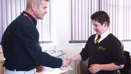 Author Terry Sewell handing out a prize to Year Seven student Dylan English at the Fakenham Academy,