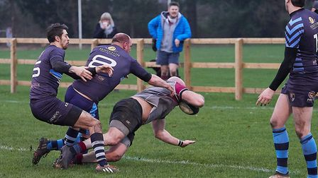 West Norfolk's No 8 Jamie Williamson scores the first try of the game despite the close attentions o