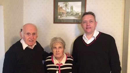 George, Sheila and Douglas Johnson at Reepham Post Office and stores, with George's painting behind