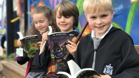 Alice, Freddie and Billy, dressed up like hogwarts students, reading Harry Potter outside their new