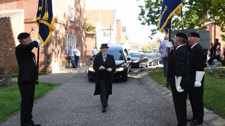 The hearse is greeted by Royal British Legion standard bearers for the funeral of stock car racing l