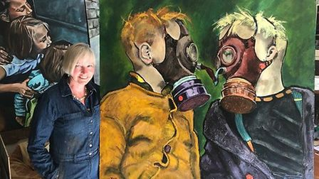 Terri Broughton with the painting of two children wearing gas masks looking at each other. Pictures:
