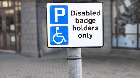 Disabled parking space sign post for badge holders only at shopping mall