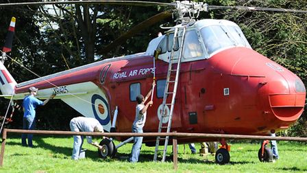 American servicemen and women with their children helping clean the historic aircraft at the Norfolk