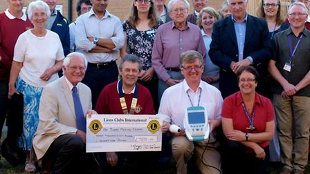 The bladder scanner at Bungay Medical Centre and the cheque, with doctors, nurses, Lions members and