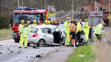 Police and firefighters at the scene of the crash at East Winch, which claimed three lives. Picture: