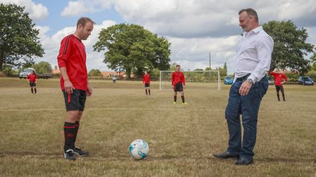 Robert Fleck carries out the ceremonial kick off with Woodton FC player/manager James Roberts. Pictu