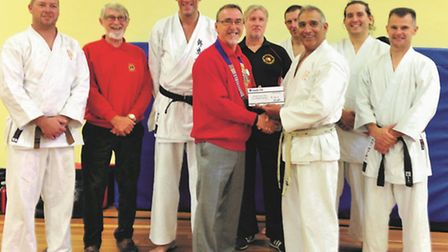 Beccles Lions president Keith Moore receiving the cheque from Shukokai Karate Group chief instructor