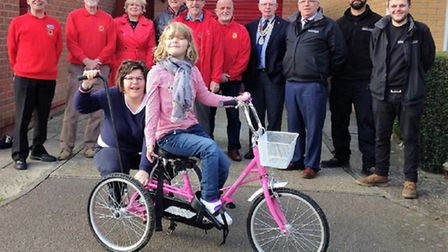 Amelia Brown and her mother with the new trike and representatives of the groups which helped pay fo