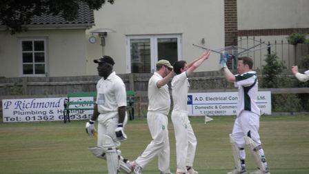 Dereham A's Neal Widdows celebrates one of his six wickets with wicket-keeper Neil Burrage after bow