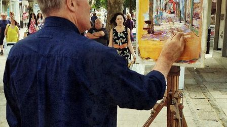 Mr Patchett painting in Norwich market. His work will be displayed at The Forum from August 8 to 12.