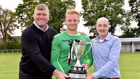 Former Norwich City player Rob Newman and Matthew Humby present the cup to Beccles Town captain Dann