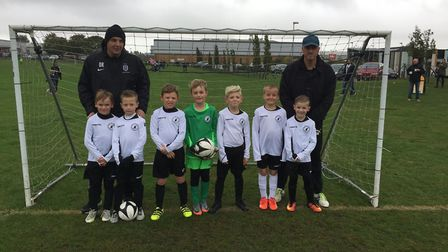 Coaches Daniel Riches (left) and Mike Pritchard with Beccles Town FC U8 in their new kit. Picture: J