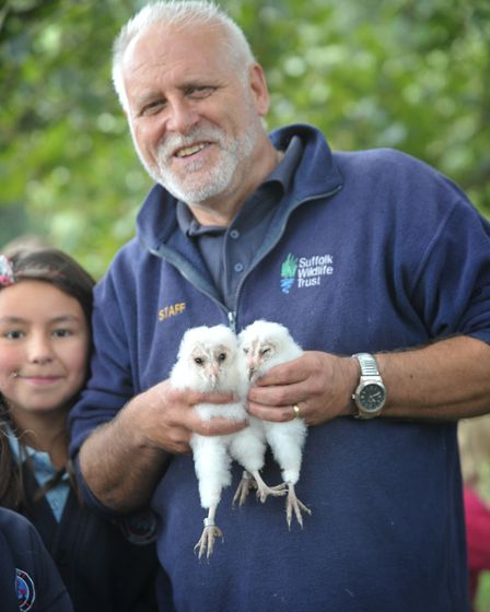 Steve Piotrowski with two barn owl chicks. Picture: SARAH LUCY BROWN