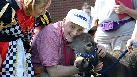 Britten Court's Stan Ellingham with a minature donkey at Care Home Open Day. Photo courtesy of Britt