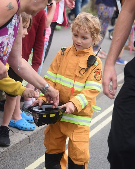 A young fire fighter shakes the bucket at the Beccles Carnival parade. Picture: DENISE BRADLEY