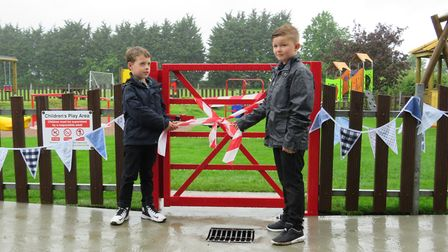 Charlie Davis and his friend pull the ribbon to mark the reopening of the Ringsfield and Weston Play