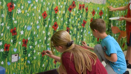 Two students put the finishing touches on some of the mural's flowers. Photo: Matthew Nixon