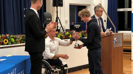 Former student Lochlann Baker receives his award from para-triathlete Joe Townsend at the SET Beccle
